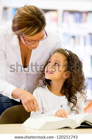 Teacher guiding a young student at the school - stock photo