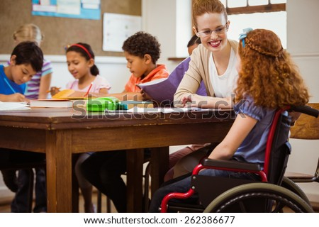 Teacher helping a disabled pupil at the elementary school - stock photo
