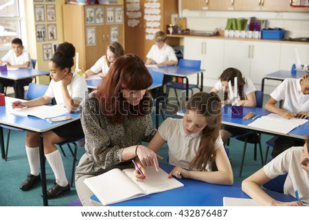 Teacher helping a girl with work at her desk, elevated view - stock photo