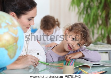 Teacher helping a pupil with her school work - stock photo