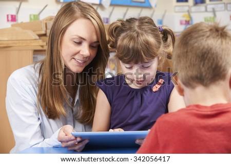 Teacher Helping Elementary School Pupil Use Digital Tablet - stock photo