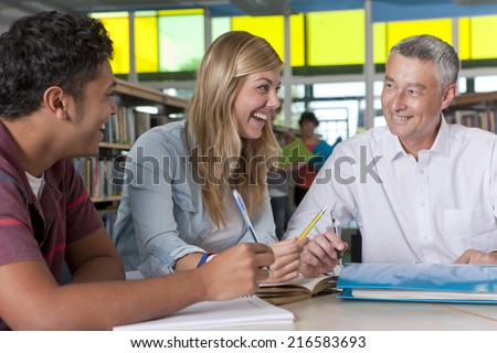 Teacher helping in study group with students in school library - stock photo