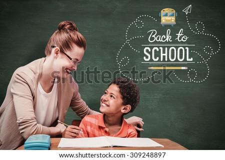 Teacher helping pupil against green chalkboard - stock photo