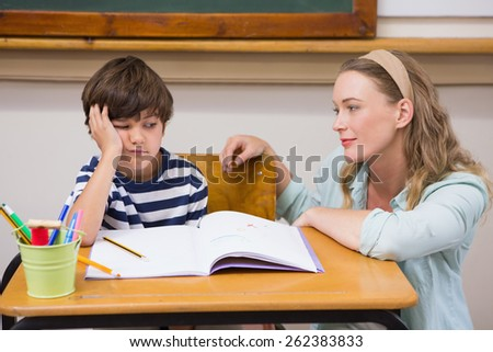 Teacher helping pupil at elementary school - stock photo