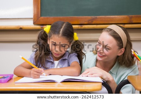 Teacher helping pupil in classroom at elementary school - stock photo
