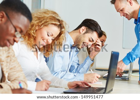 Teacher helping some students in a class in the university - stock photo
