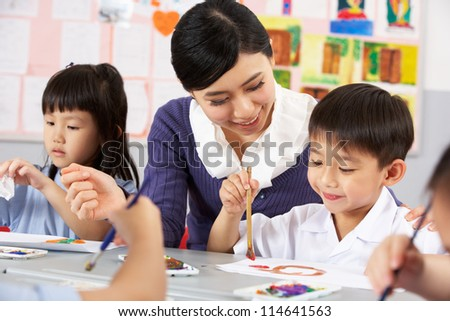 Teacher Helping Students During Art Class In Chinese School Classroom - stock photo