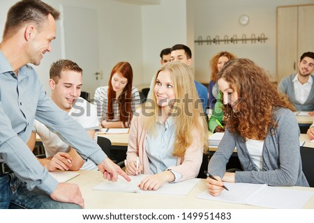 Teacher helping students in university seminar class - stock photo