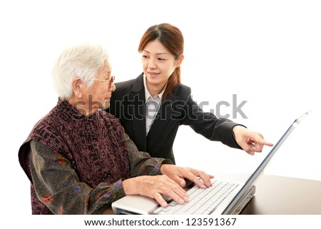 Teacher helping students on the computer - stock photo