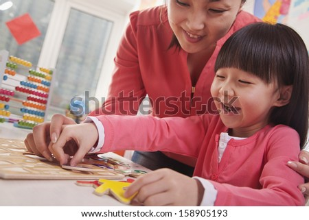 Teacher helping young girl with cut-out alphabet letters - stock photo