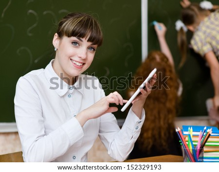 Teacher holding a tablet computer at classroom. looking at camera - stock photo
