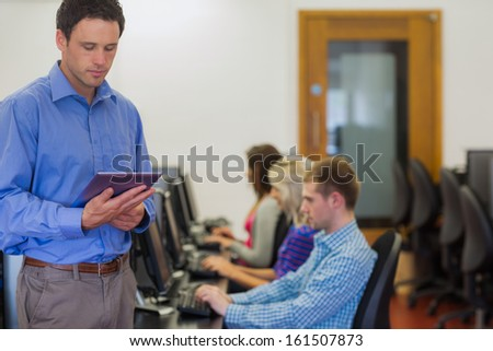 Teacher holding tablet PC with young college students using computers in the computer room - stock photo