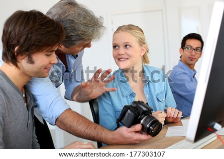 Teacher in class of photography with students - stock photo
