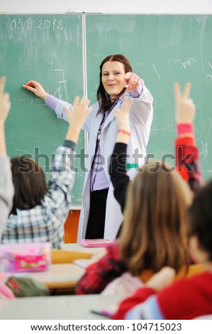 Teacher in classroom and looking at students who raised their arms - stock photo