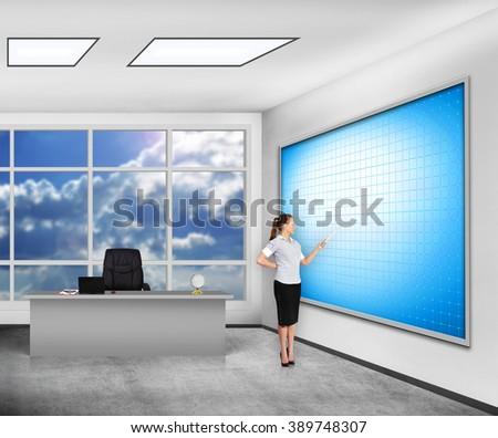 teacher in classroom pointing on blank plasma panel - stock photo
