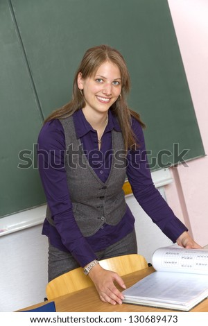 Teacher in front of a classroom. Young attractive teacher. - stock photo
