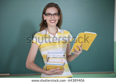 Teacher in front of blackboard holding books - stock photo