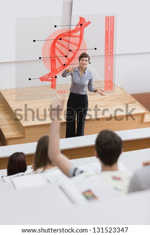 Teacher in front of futuristic interface pointing college student in lecture hall - stock photo