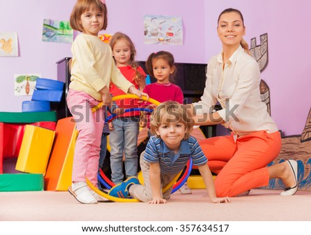 Teacher, kids in kindergarten play game with hoop - stock photo