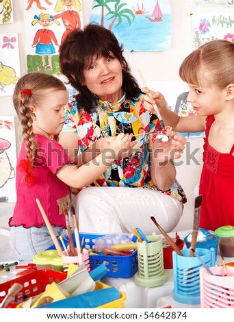 Teacher learn children painting picture  in preschool. - stock photo