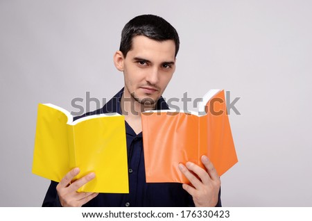 Teacher looking at the books with suspicion. Student wondering. Man holding two books with orange and yellow blank covers. - stock photo