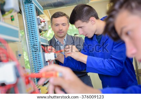 Teacher observing students working on electrical circuits - stock photo