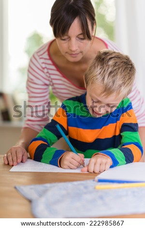 Teacher or concerned mother looking over the shoulder of a young boy as he sits at a table writing or drawing on a sheet of paper - stock photo