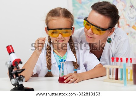 Teacher overseeing chemical experiment in elementary school science class - stock photo