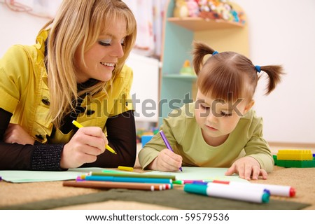 Teacher play with cute child in preschool - stock photo