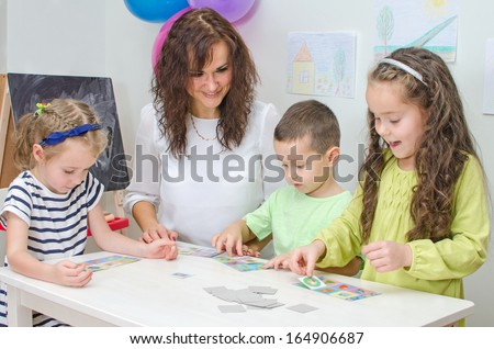 Teacher plays with children in kindergarten. - stock photo