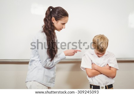 Teacher punishing the bold student at the elementary school - stock photo