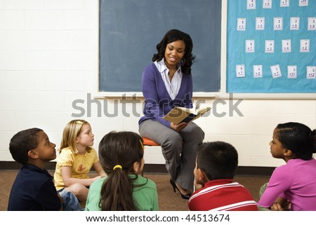 Teacher reading book to young students in classroom. Horizontally framed shot. - stock photo