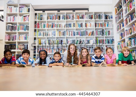 Teacher reading books to her students at school - stock photo