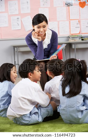 Teacher Reading To Students In Chinese School Classroom - stock photo