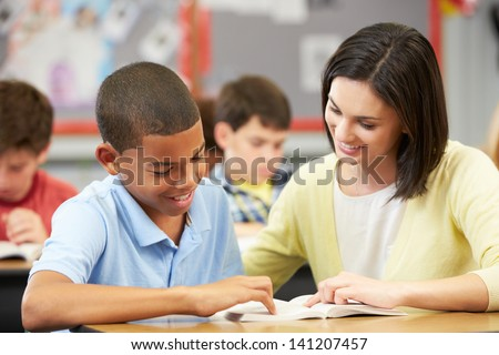 Teacher Reading With Male Pupil In Class - stock photo