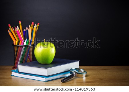 Teacher's desk with a color pencil, notebook and other equipment. - stock photo