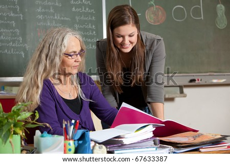 Teacher showing her student something from behind her desk - stock photo