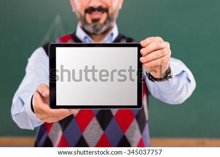 Teacher showing tablet in classroom. - stock photo
