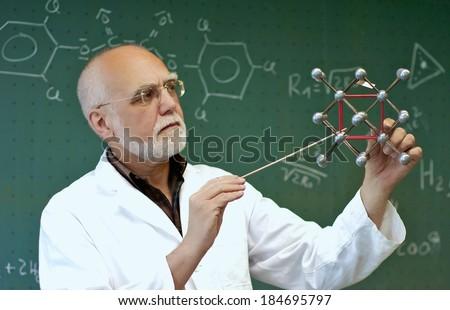 Teacher shows the class a little at a molecular model - stock photo