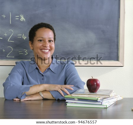 Teacher sitting at her desk - stock photo