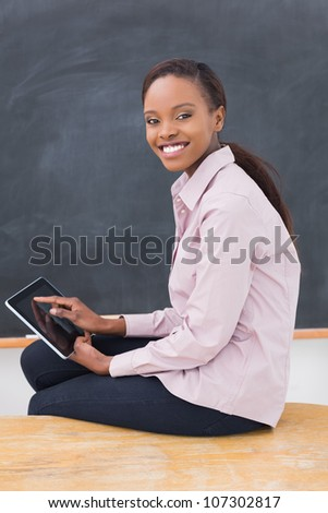 Teacher sitting on desk while holding a tablet computer in a classroom - stock photo
