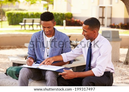 Teacher Sitting Outdoors Helping Male Student With Work - stock photo
