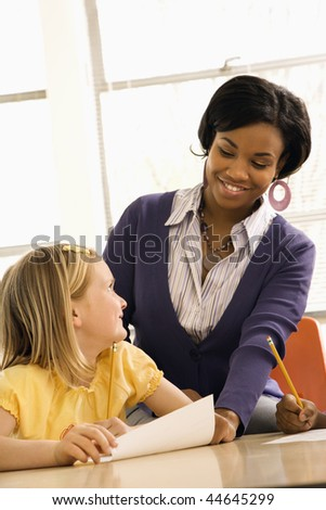 Teacher smiling and helping students with schoolwork in school classroom. Vertically framed shot. - stock photo