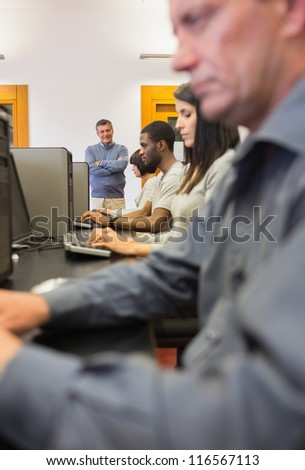 Teacher standing and smiling in computer class in college - stock photo