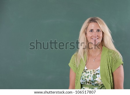 Teacher standing in front of chalkboard of classroom. Copy space can be used on chalkboard. - stock photo