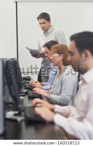 Teacher standing in front of computer class in college - stock photo