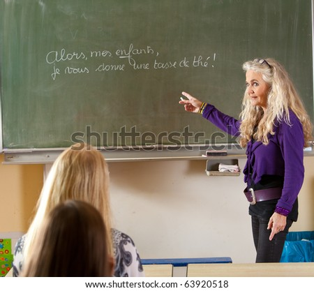 Teacher standing in front of the classroom teaching french - stock photo