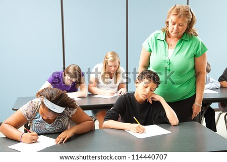 Teacher supervising students who are taking a standardized achievement test. - stock photo