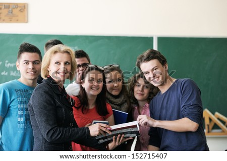 Teacher surrounded by her students in classroom holding a copybook - stock photo