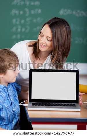 Teacher teaching cheerful student from laptop in the classroom - stock photo